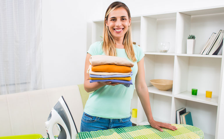 Woman ironing at an ironing board while smiling